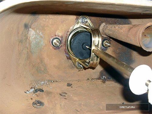 Шток (на фото справа внизу) проходит сквозь крышку. Полый винт с широкой пластиковой шайбой под ним фиксирует крышку.