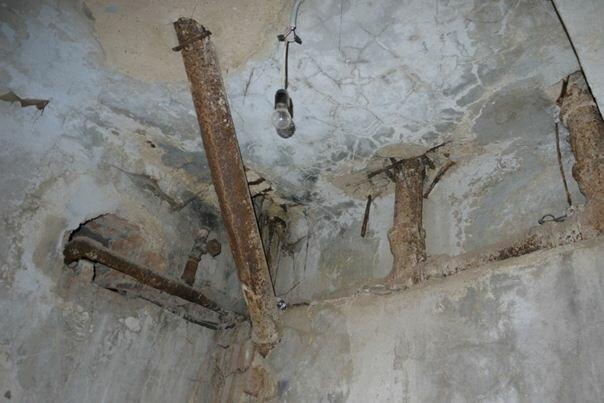 Трап, ведущий к унитазу на первом этаже, украшает потолок подвала
