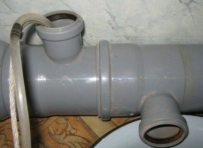 Введение шланга для подачи горячей воды внутрь канализационной трубы